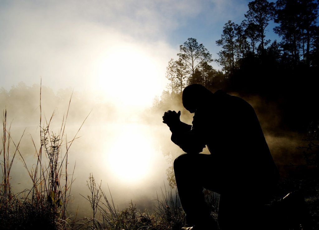 man praying in the morning at a pond